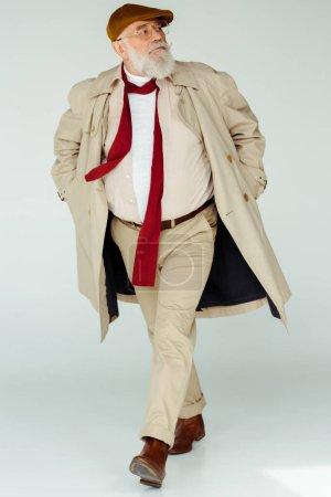 Photo pour Pleine longueur d'un bel homme âgé en manteau de tranchée marchant sur fond blanc - image libre de droit