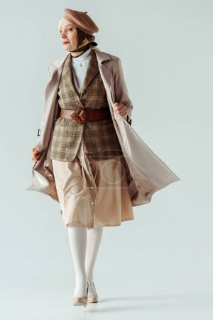 Full length of elegant senior woman in trench coat and beret walking on white background