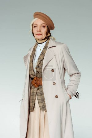 Photo pour Femme âgée à la mode en béret et en manteau de tranchée regardant la caméra isolée sur gris - image libre de droit