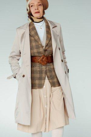 Photo pour Une dame âgée de style, les mains dans des poches de manteau, regardant loin, isolée sur - image libre de droit