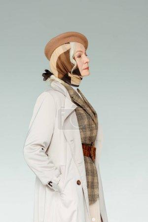 Photo pour Vue latérale d'une élégante dame âgée vêtue d'un manteau et d'un béret - image libre de droit