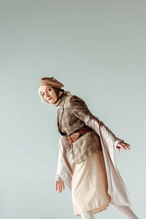 Photo pour Vue latérale d'une femme âgée élégante vêtue d'un manteau de tranchée et d'un béret regardant une caméra isolée sur - image libre de droit