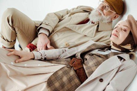 Photo pour Élégant couple d'aînés en manteau de tranchée couché sur fond blanc - image libre de droit