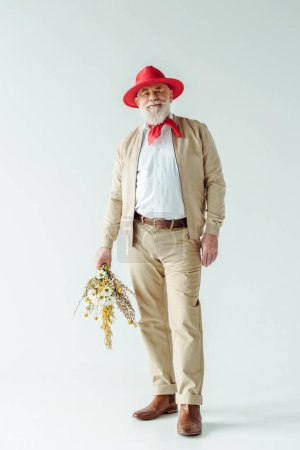 Photo for Full length of stylish senior man in red hat smiling at camera and holding wildflowers on white background - Royalty Free Image