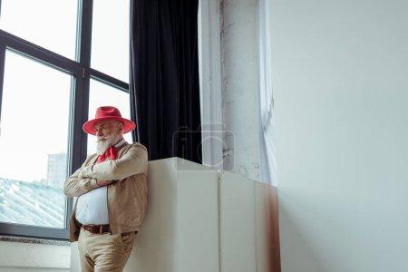 Stylish senior man in red hat standing near window in photo studio