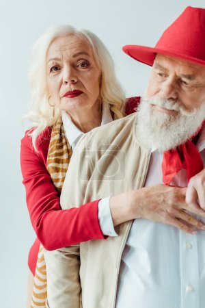 Photo for Selective focus of elegant senior woman embracing handsome man in red hat isolated on white - Royalty Free Image