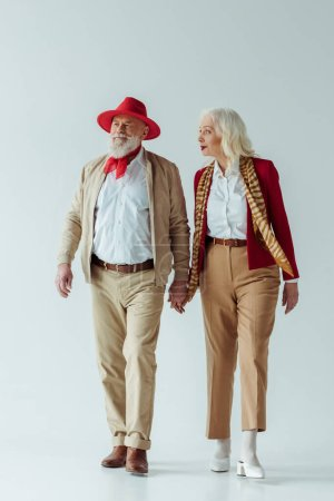 Photo for Full length of stylish elderly couple holding hands on white background - Royalty Free Image