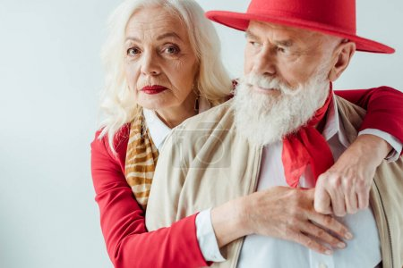 Photo pour Selective focus of elegant elderly woman looking at camera while embracing handsome senior man isolated on white - image libre de droit