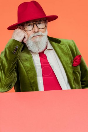Photo for Fashionable elderly man in jacket and eyeglasses looking at camera isolated on coral - Royalty Free Image