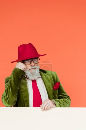 Photo for Handsome senior man in jacket and hat looking away on white background isolated on coral - Royalty Free Image