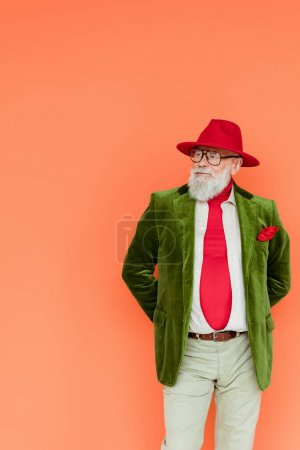 Photo for Fashionable elderly man in hat and eyeglasses looking away isolated on coral - Royalty Free Image