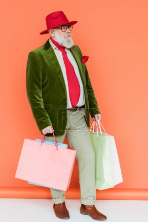 Photo for Full length of stylish senior man holding shopping bags on white surface on coral background - Royalty Free Image