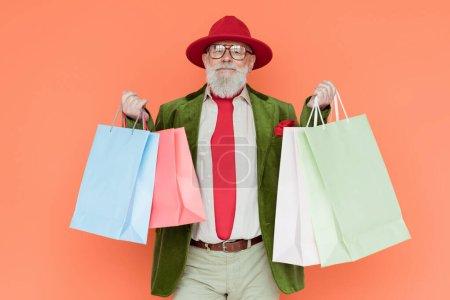 Photo pour Un homme âgé élégant tenant des sacs à provisions et regardant une caméra isolée sur un corail - image libre de droit