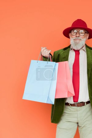 Photo for Handsome senior man in hat and eyeglasses holding shopping bags and looking at camera isolated on coral - Royalty Free Image