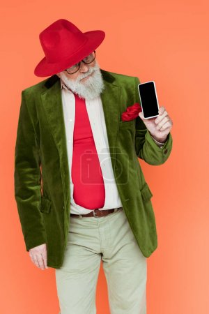 Photo for Stylish senior man looking at smartphone isolated on coral - Royalty Free Image