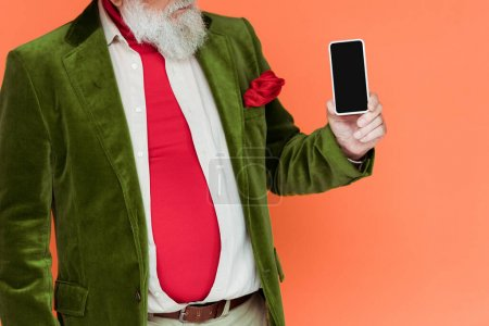 Photo for Cropped view of stylish senior man holding smartphone with blank screen isolated on coral - Royalty Free Image