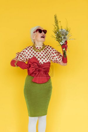 Photo for Fashionable elderly woman holding wildflowers isolated on yellow - Royalty Free Image