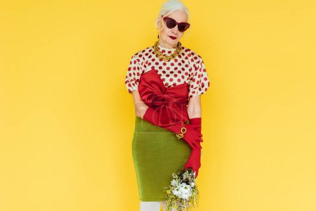 Photo for Beautiful elderly woman in sunglasses holding bouquet of wildflowers isolated on yellow - Royalty Free Image