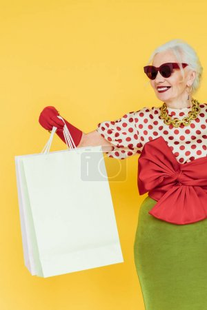 Photo for Stylish elderly woman smiling while holding shopping bags isolated on yellow - Royalty Free Image