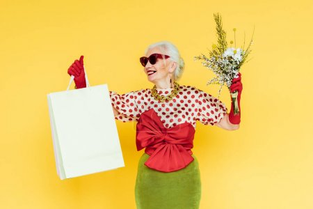 Photo for Fashionable senior woman smiling while holding wildflowers and shopping bags on yellow background - Royalty Free Image