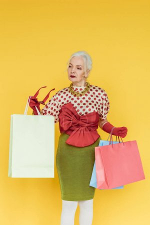 Photo for Fashionable senior woman holding shopping bags and sunglasses isolated on yellow - Royalty Free Image