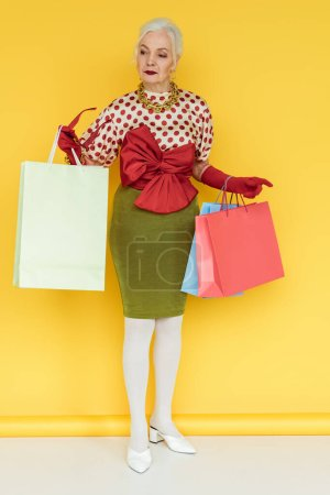 Photo for Full length of stylish senior woman with shopping bags and sunglasses looking away on white surface on yellow background - Royalty Free Image