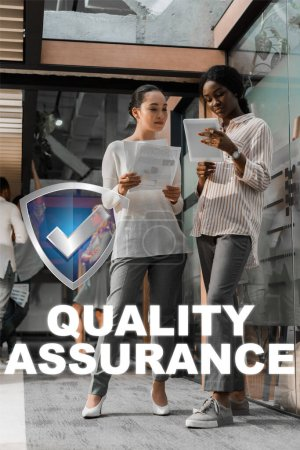 concentrated african american and asian businesswomen with digital tablet and documents standing in office with multicultural colleagues on background, quality assurance illustration