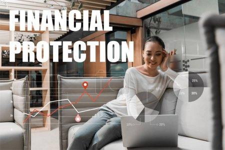 Photo pour Foyer sélectif de sourire asiatique femme d'affaires assis sur le canapé et en utilisant un ordinateur portable, illustration de protection financière - image libre de droit