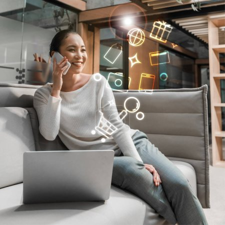 Photo for Cheerful asian businesswoman talking on smartphone while sitting on couch near laptop, digital icons illustration - Royalty Free Image