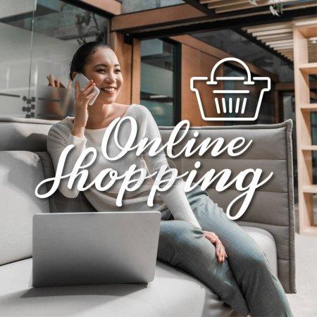 Photo pour Joyeuse asiatique femme d'affaires parler sur smartphone tout en étant assis sur le canapé près d'un ordinateur portable, illustration achats en ligne - image libre de droit