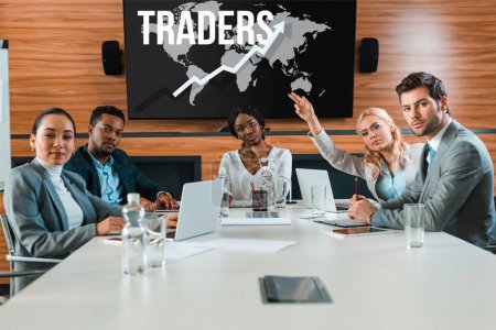 young businesswoman raising hand while sitting in conference hall near multicultural colleagues looking at camera, traders illustration