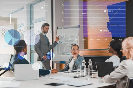 handsome businessman pointing with finger at flipchart with infographics while multicultural colleagues sitting at desk in conference hall, charts and graphs illustration