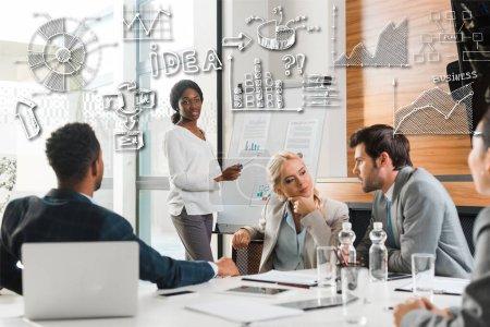 Photo pour Séduisante femme d'affaires africaine-américaine se tenant près du tableau à feuilles mobiles avec infographie tandis que ses collègues multiculturels s'assoient au bureau, illustration d'affaires - image libre de droit