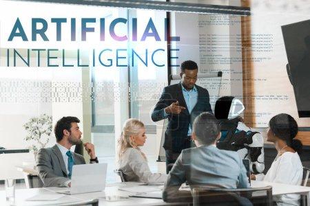 Photo pour Bel homme d'affaires africain américain montrant un robot à des collègues multiculturels en poste, illustration d'intelligence artificielle - image libre de droit
