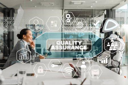 Foto de Vista lateral de las sonrientes empresarias asiáticas hablando con robots en la sala de conferencias, ilustración de la garantía de calidad. - Imagen libre de derechos