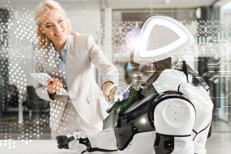 Photo pour Une femme d'affaires souriante utilisant un robot tout en tenant une tablette numérique, illustration de la cybersécurité - image libre de droit