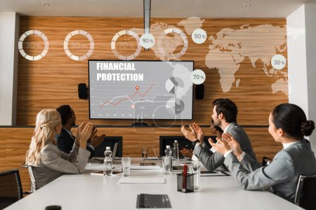 Photo for Young multicultural businesspeople applauding while sitting in conference hall and looking at lcd screen on wall, financial protection illustration - Royalty Free Image