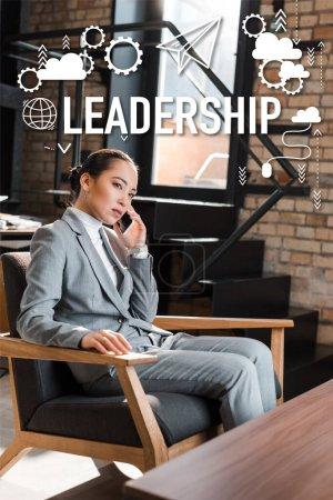 Photo pour Sérieux asiatique femme d'affaires assis dans fauteuil et parler sur smartphone, leadership illustration - image libre de droit
