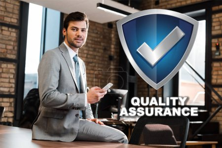 handsome, positive businessman sitting on office desk, holding smartphone and looking at camera, quality assurance illustration