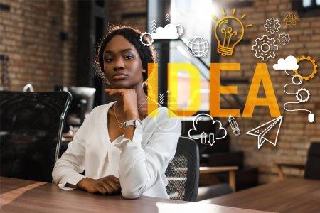 Photo pour Séduisante femme d'affaires afro-américaine réfléchie assise au bureau et regardant la caméra, illustration d'idée - image libre de droit