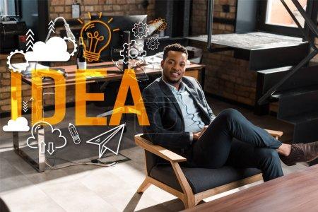 Photo pour Homme d'affaires afro-américain souriant assis dans un fauteuil et regardant la caméra, illustration d'idée - image libre de droit