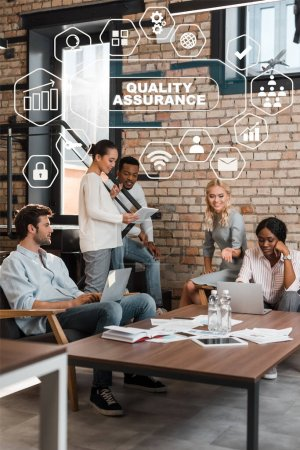 Photo for Young multicultural businesspeople with gadgets having brainstorming in office, quality assurance illustration - Royalty Free Image