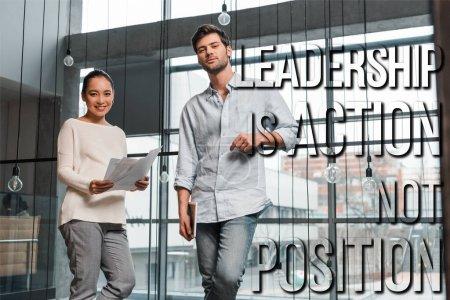 Photo pour Femme d'affaires asiatique enceinte tenant des papiers tout en se tenant près de beau collègue, illustration de leadership - image libre de droit