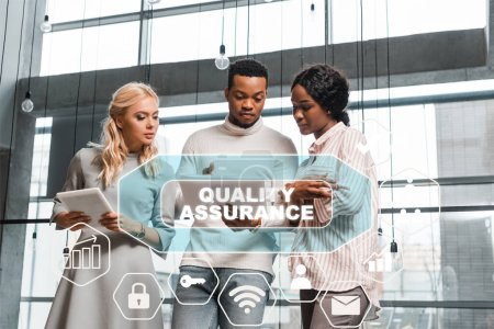young businesswoman holding digital tablet while standing near african american colleagues looking at documents, quality assurance illustration