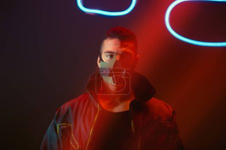 Photo pour Cyberpunk bi-racial joueur en masque de protection en regardant la caméra près de néon éclairage sur noir - image libre de droit