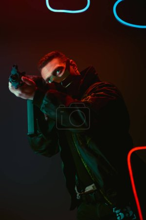 Photo for Bi-racial cyberpunk player in protective mask aiming gun near neon lighting on black - Royalty Free Image