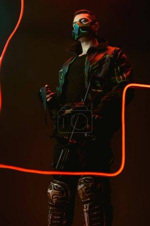 Foto de Peligroso ciberpunk biracial en una máscara protectora con pistola cerca de la iluminación de neón sobre negro. - Imagen libre de derechos