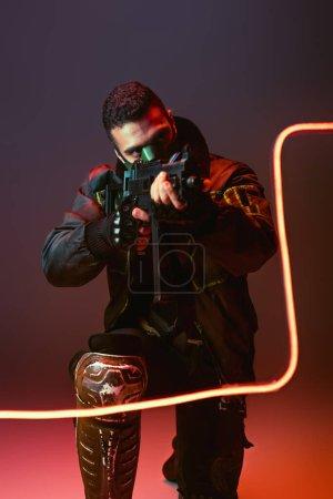 Photo pour Cyberpunk bi-racial man in mask aiming gun near neon lighting on black - image libre de droit