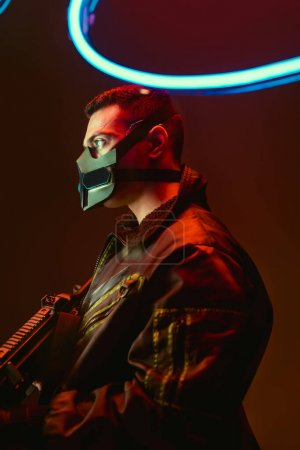 Photo for Bi-racial cyberpunk player in mask holding gun near blue neon lighting on black - Royalty Free Image