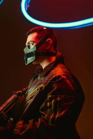 Photo for Bi-racial cyberpunk player in mask holding gun near blue neon lighting on black - Royalty Free Image